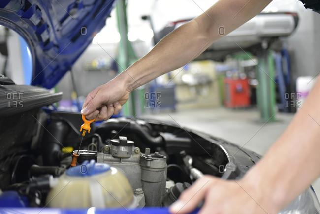 Car mechanic in a workshop checking motor oil