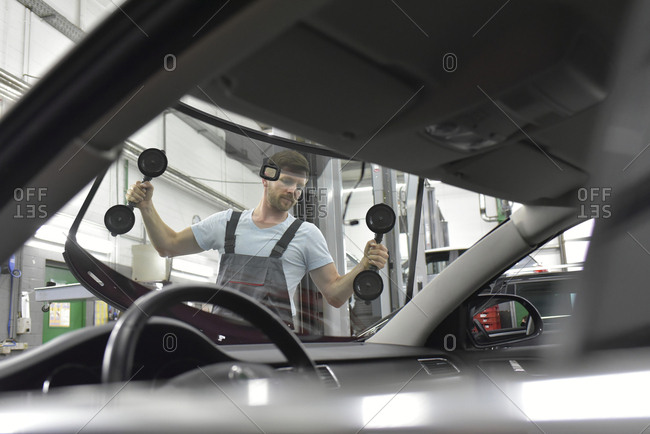 Car mechanic in a workshop changing car window