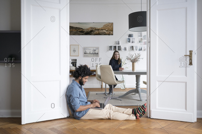 Man at home sitting on floor working with laptop with woman in background