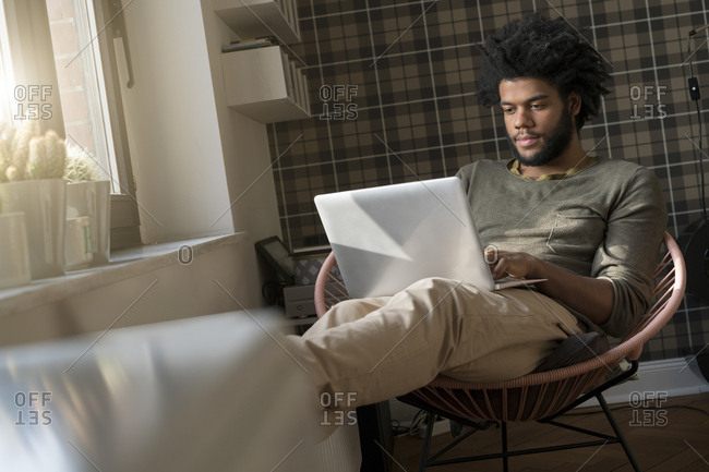 Man sitting in living room in armchair working on laptop