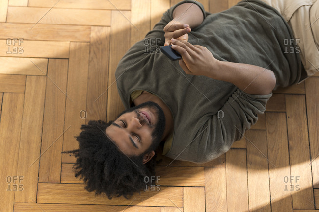 Man lying on floor with smartphone