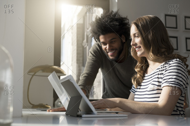 Smiling couple working at home with laptop and tablet