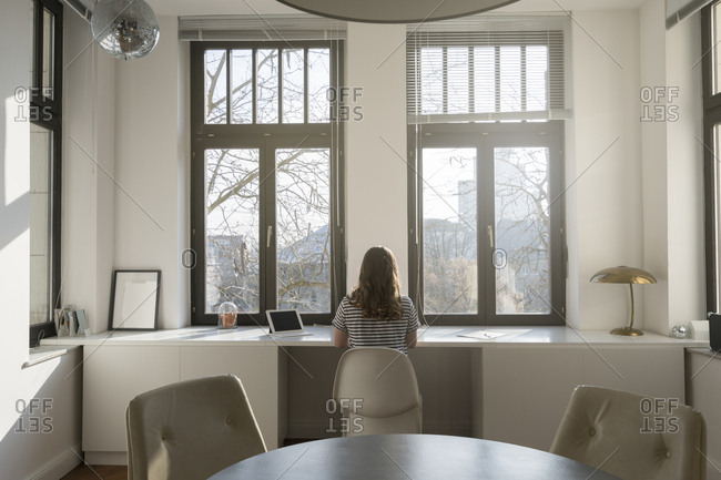 Woman in front of panorama window at home with tablet