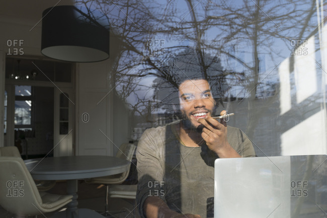 Man speaking on smartphone in front of laptop at the window