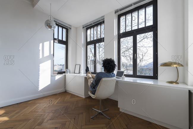 Man sitting in minimalist empty room on chair