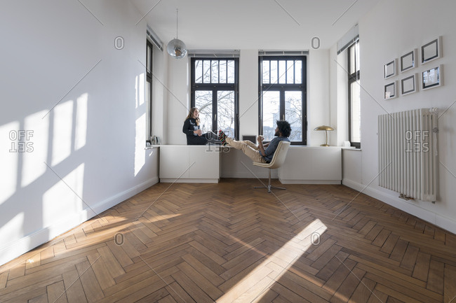 Smiling couple sitting in minimalist empty room talking
