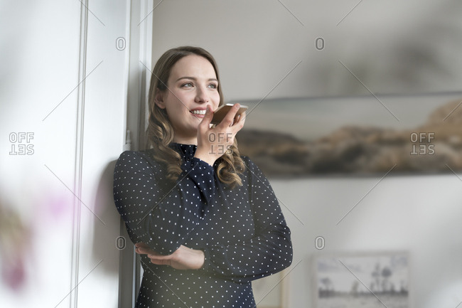 Smiling woman at home leaning in door frame speaking into smartphone