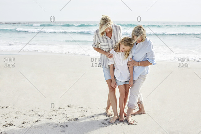 Mother - daughter and grandmother standing in a heart - drawn into the sand on the beach