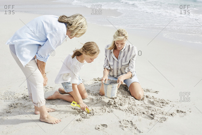 Family playing with sand on the beach