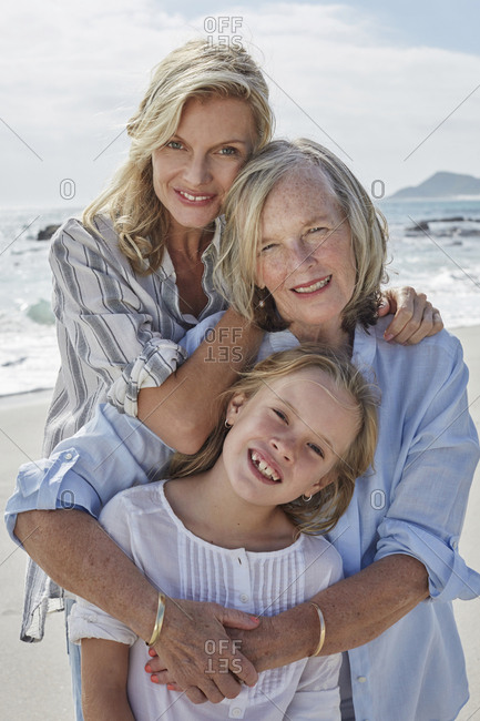 Mother - daughter and grandmother embracing on the beach