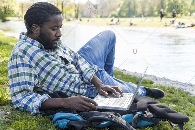 Man on a meadow using laptop