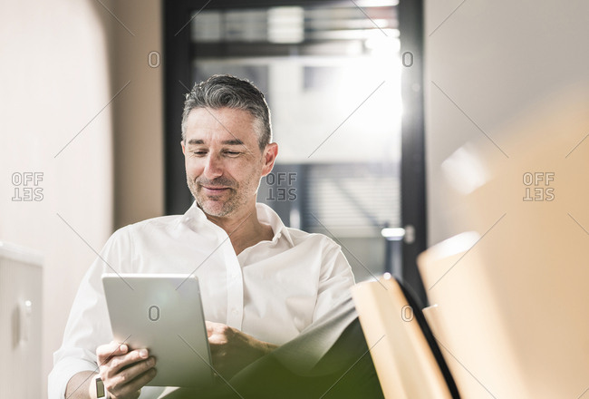 Content businessman sitting in his office using tablet