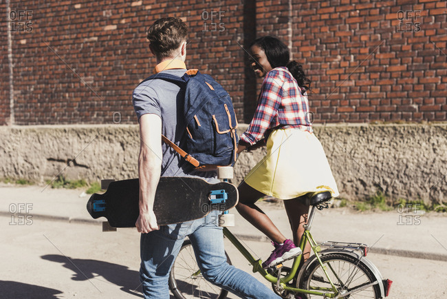 Young couple with bicycle and skateboard walking in the street