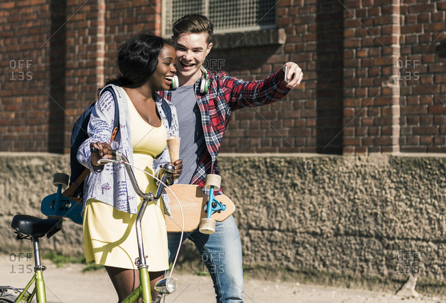 Young couple with bicycle and skateboard taking smartphone selfie