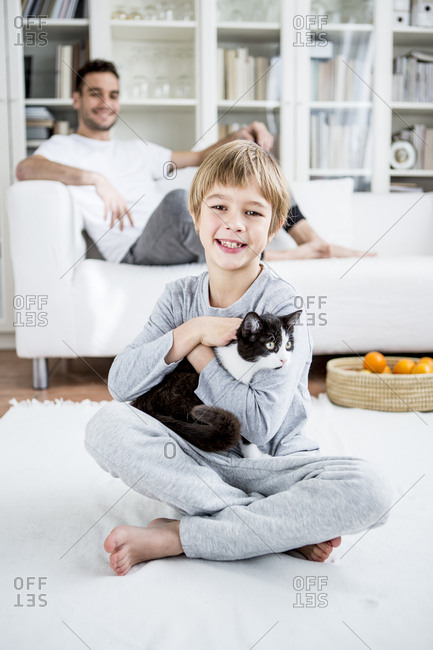 Smiling boy caressing cat at home