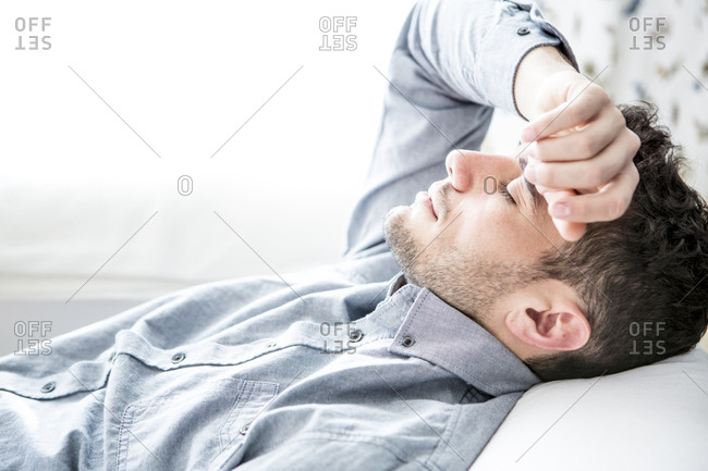 Man lying on couch with closed eyes