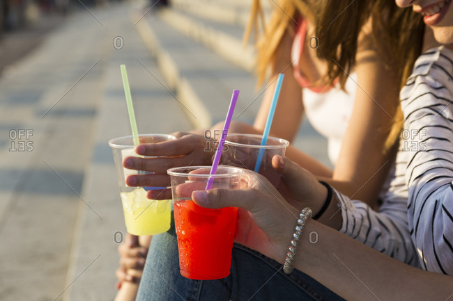 Three young women with soft drinks - partial view
