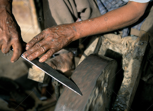 Hands of a man sharpening a knife