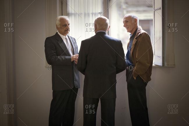 Three senior men talking