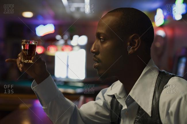 Young man holding a shot of liquor at a bar