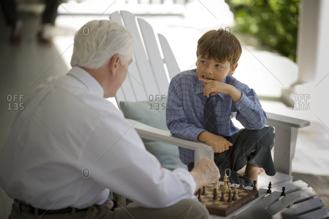 Boy playing chess with his grandfather