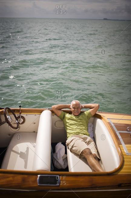 Senior man reclining in a motorboat