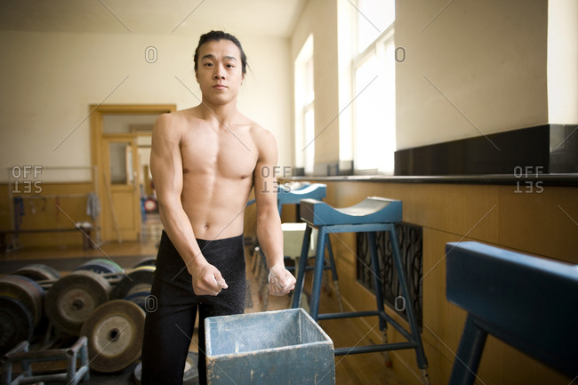 Shirtless young man putting chalk on his hands in a gymnasium