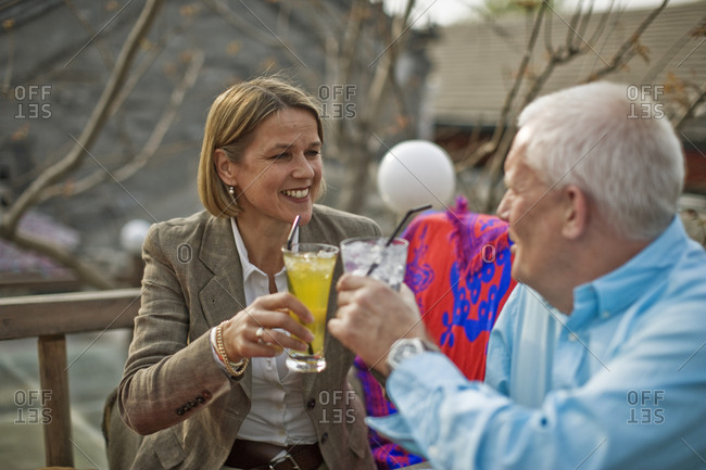 Man and woman toasting with drinks