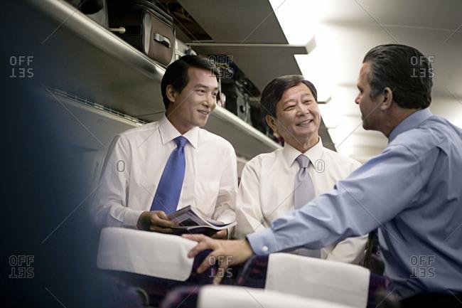 Businessmen talking in an airplane