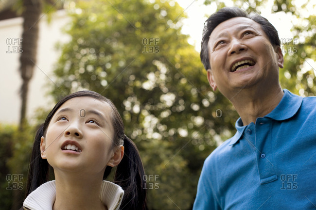 A girl and her grandfather looking up