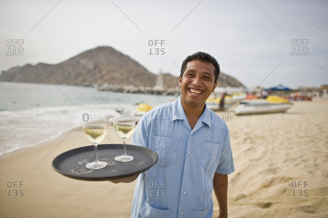 Smiling waiter holding a tray of wine glasses on a beach