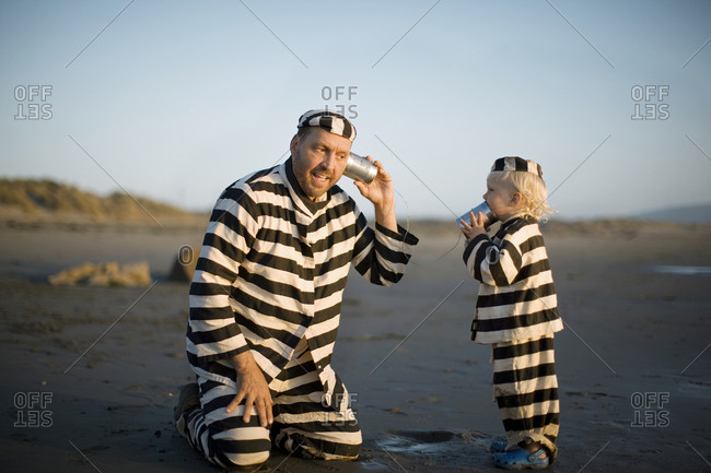 Father and son dressing as prisoners while playing with tin cans on a beach