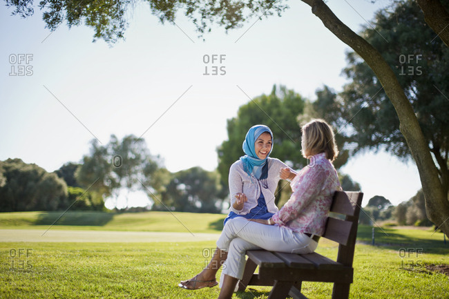 Friends talking on a park bench