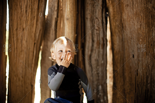 Boy yawning by tree trunks