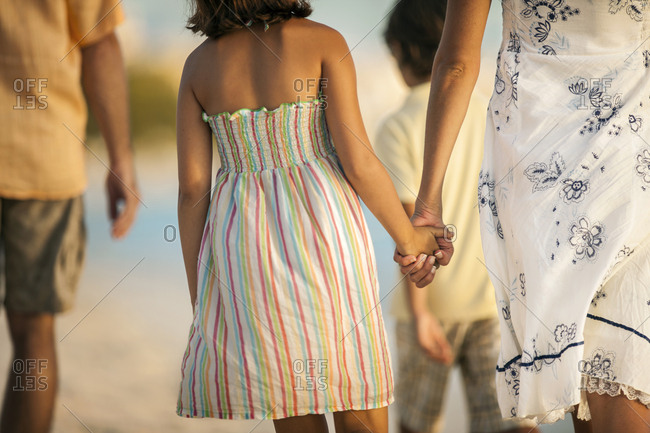 Rear view of a mother and daughter walking hand in hand