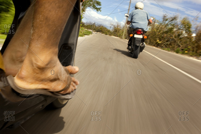 Foot of a man riding a scooter