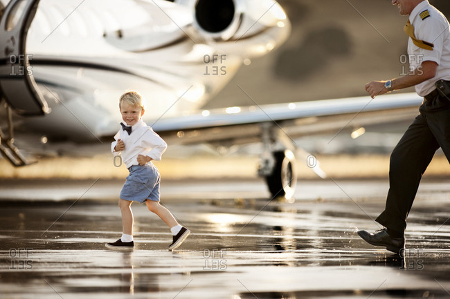 Smiling boy running from a pilot on a runway