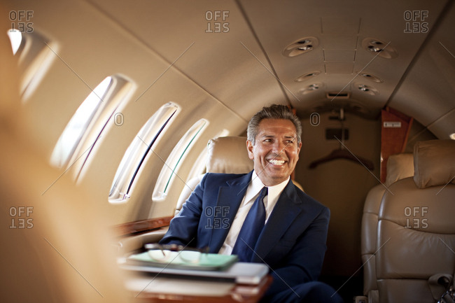 Smiling businessman on a private jet