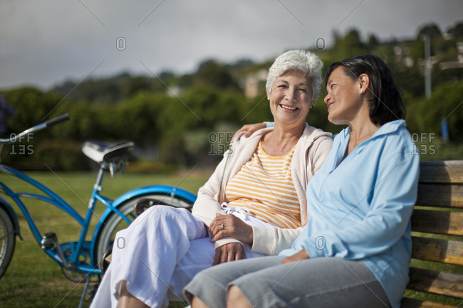 Smiling women sitting on a park bench
