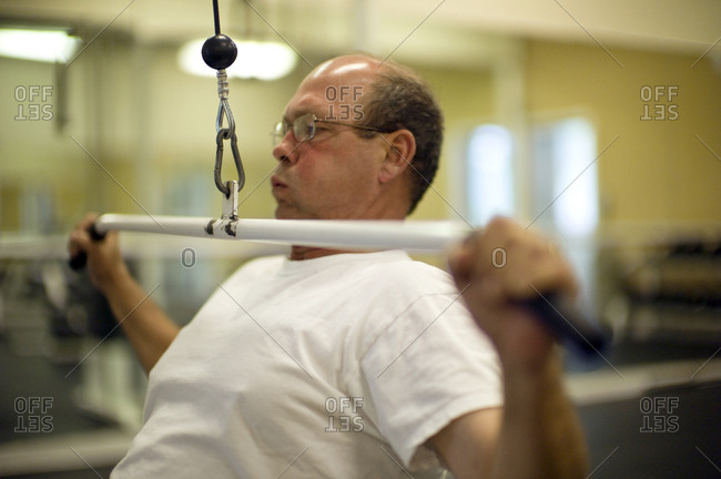 Middle aged man exercising at a gym