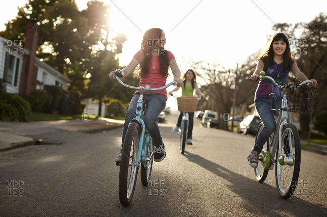 Teenage girls riding bicycles down a suburban street