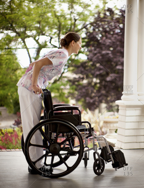 Nurse holding a wheelchair at a nursing home