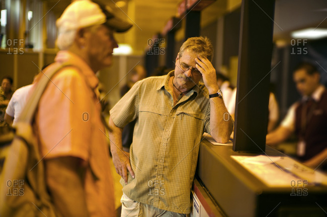 Stressed man at a ticket counter