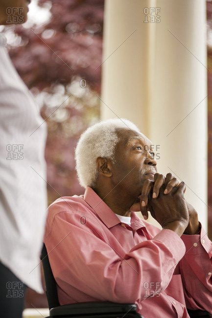 Senior man sitting with his hands clasped