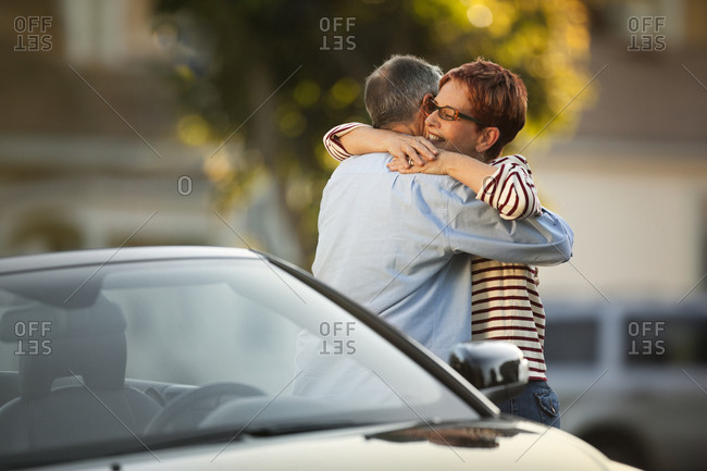 Middle aged couple hugging beside a car