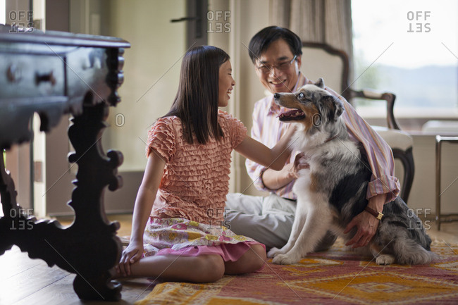 Father and daughter petting their dog