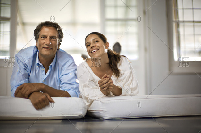 Smiling couple lying on cushions