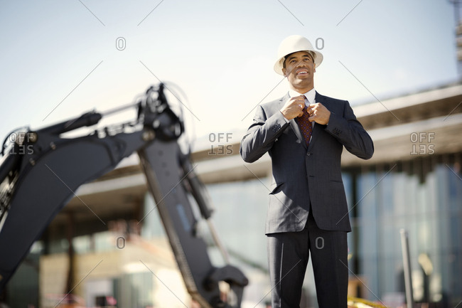 Businessman in a hard hat on a construction site