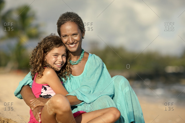 Mother and daughter sitting together on a beach