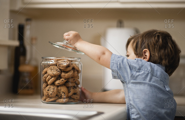 Boy lifting the lid on a cookie jar